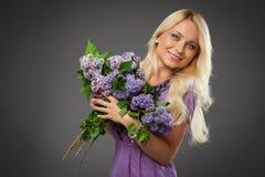 Muchacha rubia en el vestido púrpura que sostiene el ramo de lila Imagen de archivo