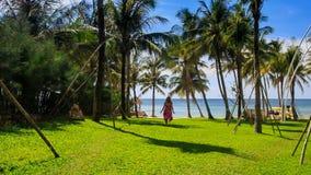 Muchacha rubia en funcionamientos del rojo a la playa a lo largo del césped en parque de la palma de la ciudad almacen de metraje de vídeo