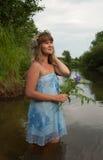Muchacha rubia en guirnalda de la flor en el río Foto de archivo libre de regalías