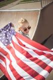 Muchacha rubia en las gafas de sol que sostienen la bandera americana mientras que se coloca en rampa en el parque del monopatín Fotos de archivo