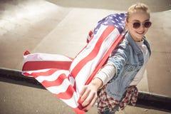 Muchacha rubia en las gafas de sol que sostienen la bandera americana mientras que se coloca en rampa en el parque del monopatín Imagen de archivo