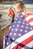 Muchacha rubia en las gafas de sol que sostienen la bandera americana mientras que se coloca en rampa en el parque del monopatín Fotografía de archivo