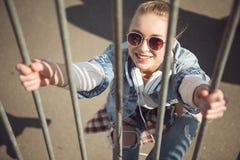 Muchacha rubia en las lentes que cuelgan en la cerca en parque del monopatín Fotografía de archivo libre de regalías