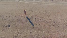 Muchacha rubia en los funcionamientos blancos del bikini a lo largo de la arena de la playa en el agua Sombras largas metrajes