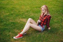 Muchacha rubia en pantalones cortos en el verano en la hierba Fotos de archivo libres de regalías