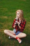 Muchacha rubia en pantalones cortos en el verano en la hierba Fotografía de archivo libre de regalías