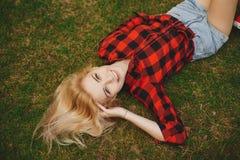 Muchacha rubia en pantalones cortos en el verano en la hierba Foto de archivo