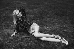 Muchacha rubia en pantalones cortos en el verano en la hierba blanco y negro Fotos de archivo libres de regalías
