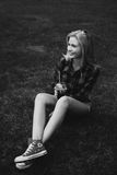 Muchacha rubia en pantalones cortos en el verano en la hierba blanco y negro Fotos de archivo