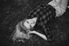 Muchacha rubia en pantalones cortos en el verano en la hierba blanco y negro Imagen de archivo libre de regalías