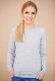 Muchacha rubia en suéter gris casual Imágenes de archivo libres de regalías