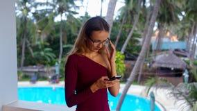 Muchacha rubia en textos de los vidrios en el teléfono contra piscina almacen de video