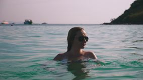 Muchacha rubia en un bañador y lentes de sol negros Modelo hermoso con nadadas del cuerpo en agua de mar azul almacen de video
