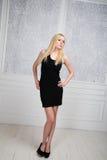 Muchacha rubia en un poco vestido negro Foto de archivo libre de regalías