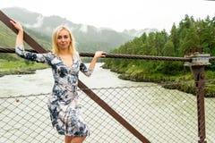Muchacha rubia en un vestido con un escote que presenta en un constr del puente imágenes de archivo libres de regalías