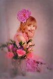 Muchacha rubia en un vestido rosado con una flor en su pelo Imagen de archivo libre de regalías