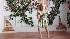 Muchacha rubia en un vestido verde descalzo que se divierte, baile, salto, haciendo girar metrajes