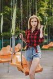 Muchacha rubia en una camisa de tela escocesa en el parque Imagenes de archivo