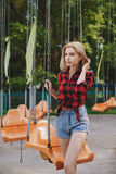 Muchacha rubia en una camisa de tela escocesa en el parque Fotografía de archivo