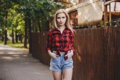 Muchacha rubia en una camisa de tela escocesa en el parque Fotos de archivo