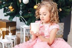 Muchacha rubia en vestido rosado debajo del árbol del Año Nuevo y miradas en una vela ardiente Fotografía de archivo libre de regalías