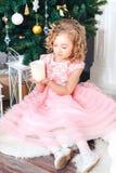 Muchacha rubia en vestido rosado debajo del árbol del Año Nuevo y miradas en una vela ardiente Imágenes de archivo libres de regalías