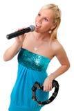 Muchacha rubia encantadora con el micrófono y la pandereta Imágenes de archivo libres de regalías