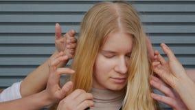 Muchacha rubia entre las palmas de manos almacen de metraje de vídeo
