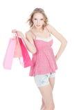 Muchacha rubia feliz con los bolsos de compras rosados Imagen de archivo libre de regalías