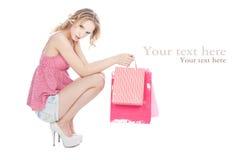 Muchacha rubia feliz con los bolsos de compras rosados Fotos de archivo