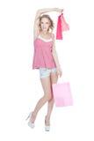 Muchacha rubia feliz con los bolsos de compras rosados Fotografía de archivo