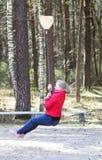 Muchacha rubia feliz del adolescente que salta con el amortiguador auxiliar en parque Foto de archivo