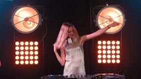 Muchacha rubia feliz hermosa de DJ en cubiertas el partido almacen de video