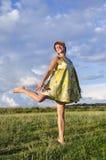 Muchacha rubia feliz que corre descalzo en hierba en parque en la hierba verde en un cielo nublado del fondo Imágenes de archivo libres de regalías