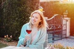 Muchacha rubia feliz que goza del vino tinto al aire libre Mujer alegre atractiva sonriente en tela escocesa hecha punto azul cla fotos de archivo libres de regalías