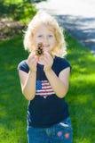 Muchacha rubia feliz que muestra apagado su pinecone. Imagen de archivo libre de regalías