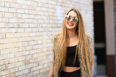 Muchacha rubia feliz que sonríe en fondo urbano Fotografía de archivo
