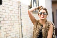 Muchacha rubia feliz que sonríe en fondo urbano Imagenes de archivo