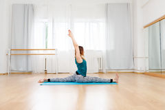 Muchacha rubia flexible que se sienta en la guita, postura de la yoga, gimnasia Fotos de archivo