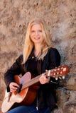 Muchacha rubia fresca que toca la guitarra al aire libre Imagenes de archivo