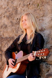 Muchacha rubia fresca que toca la guitarra al aire libre Imagen de archivo libre de regalías