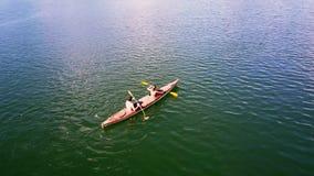 Muchacha rubia Guy Row Kayak moreno de la visión superior cercana entre el agua almacen de video
