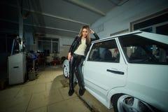 Muchacha rubia hermosa atractiva en la ropa de cuero en el garaje foto de archivo