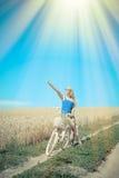 Muchacha rubia hermosa con el ciclo en el campo de trigo Fotos de archivo libres de regalías