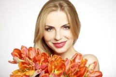 Muchacha rubia hermosa con el ramo de tulipanes aislados en un w Imagen de archivo libre de regalías