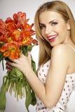 Muchacha rubia hermosa con el ramo de tulipanes aislados en un w Imagenes de archivo