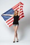 Muchacha rubia hermosa con la bandera americana Imagenes de archivo