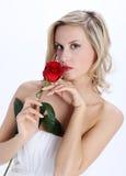Muchacha rubia hermosa con la flor de la rosa del rojo en un fondo blanco fotos de archivo libres de regalías