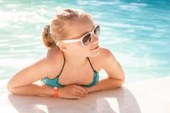 Muchacha rubia hermosa con las gafas de sol en piscina al aire libre Imagen de archivo