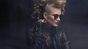 Muchacha rubia hermosa del eje de balancín en la chaqueta de cuero y las gafas de sol, presentando en el humo almacen de metraje de vídeo